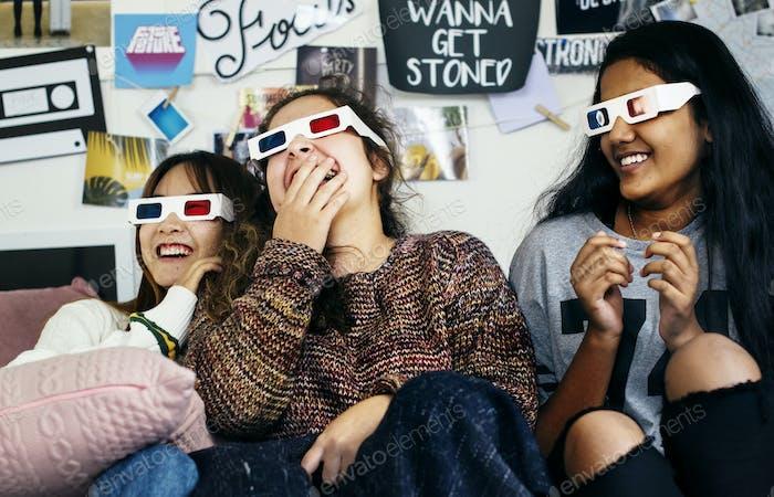 Teenage girls wearing 3d movie eyeglasses enjoying laughing and watching TV
