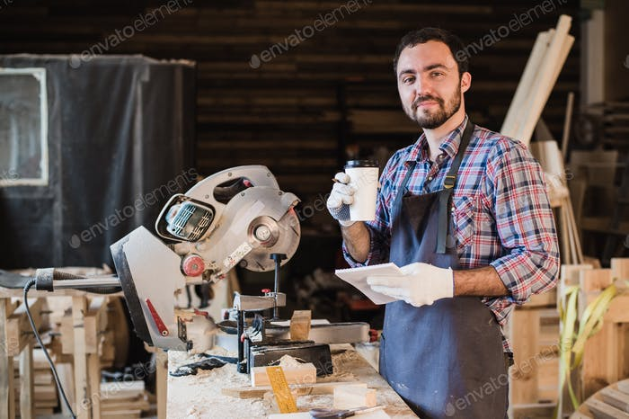 Carpenter taking a coffee break holding notebook in front of circular saw at his workshop
