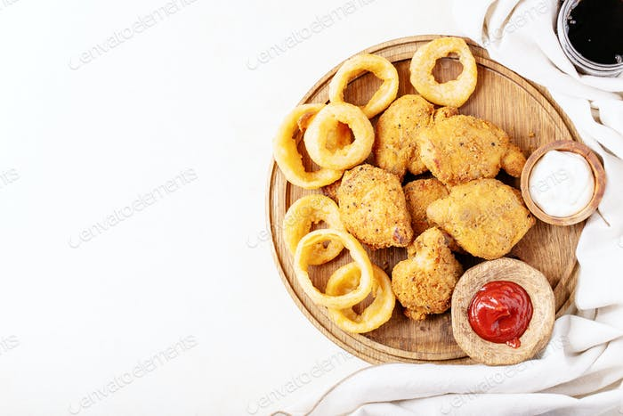 Crispy fried breaded chicken fillet with fried onion rings