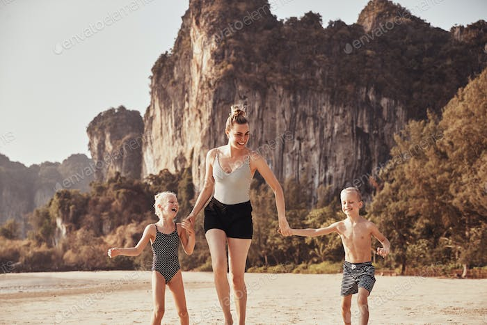 Laughing Mother holding hands with her children on a beach