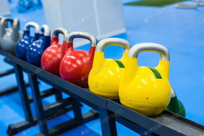 colorful kettlebells in a row in a gym - focus on the front kettlebell