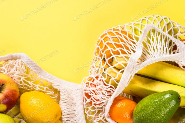 Mesh bag with fruits on color background