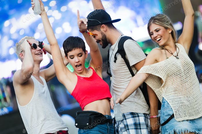 Happy friends having fun at music festival