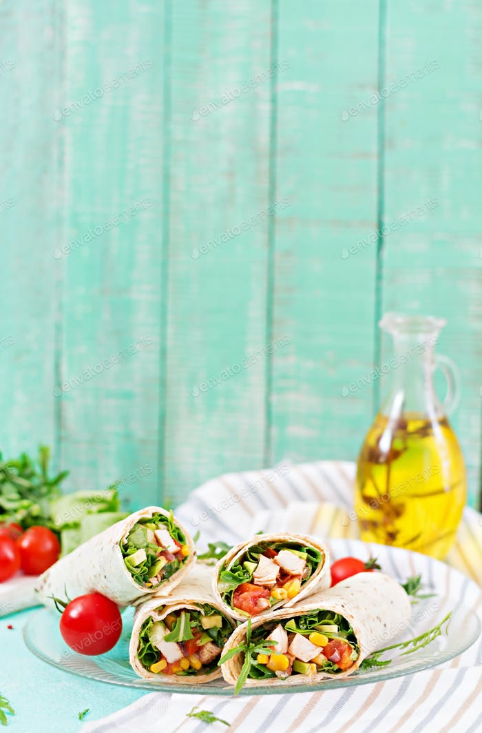Burritos wraps with chicken and vegetables on light  background. Chicken burrito, mexican food.