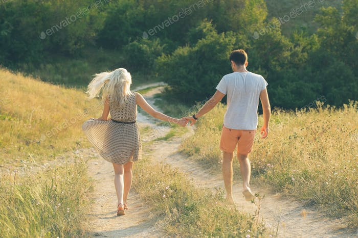 Young couple of man and woman together, hand by hand, are walking down by the field road in summer.