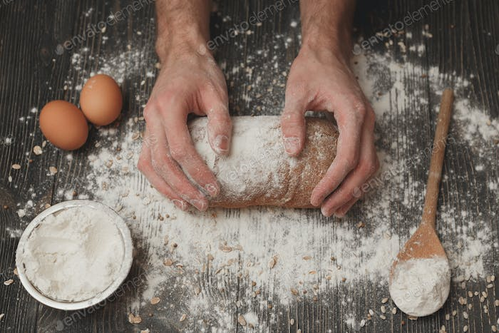 Close-up of men's baker hands on black bread with flour powder. Baking and patisserie concept