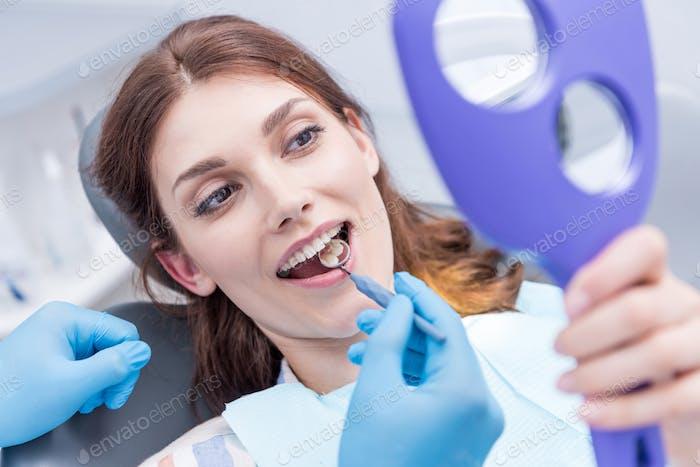 Porträt der schönen Frau Überprüfung der Zähne nach der Zähneaushärtung in der Zahnklinik