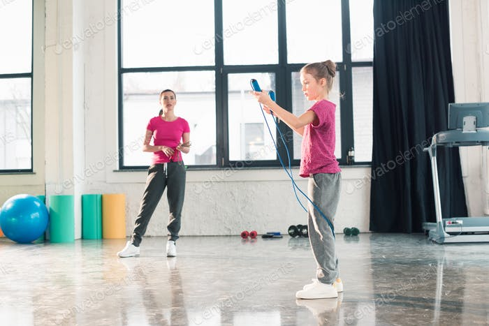 Full length view of mother looking at daughter exercising with skipping rope in gym