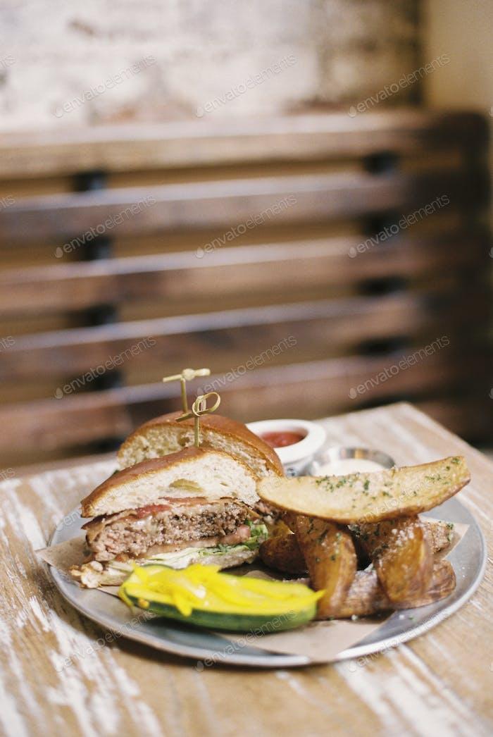 Eine Mahlzeit, ein Hamburger in einem Brötchen, Kartoffelfrites und eine Gurke.