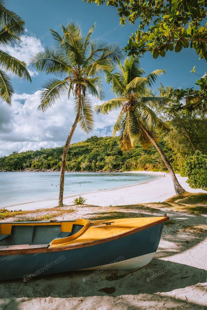 Boote am exotischen Strand Takamaka mit Palmen und blauer Ozeanlagune im Hintergrund, Mahe Insel