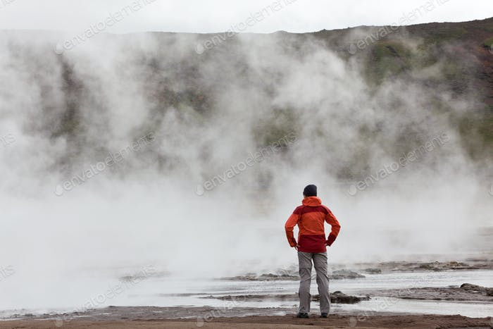 Woman standing by geothermal pools, South West Iceland