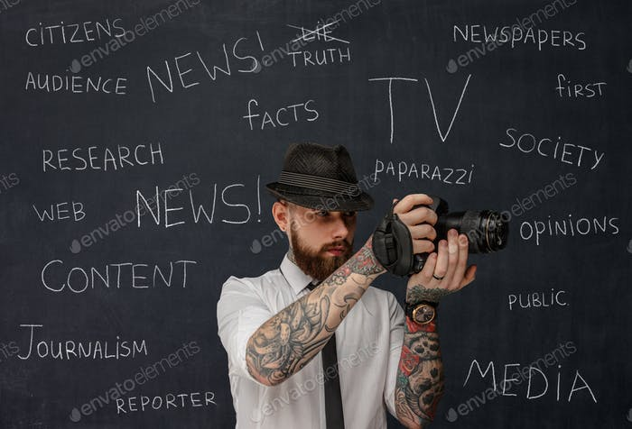 Bearded dslr photographer with tattooes on his arms.