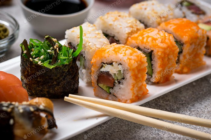 Sushi roll set with wasabi, ginger and soy sauce .
