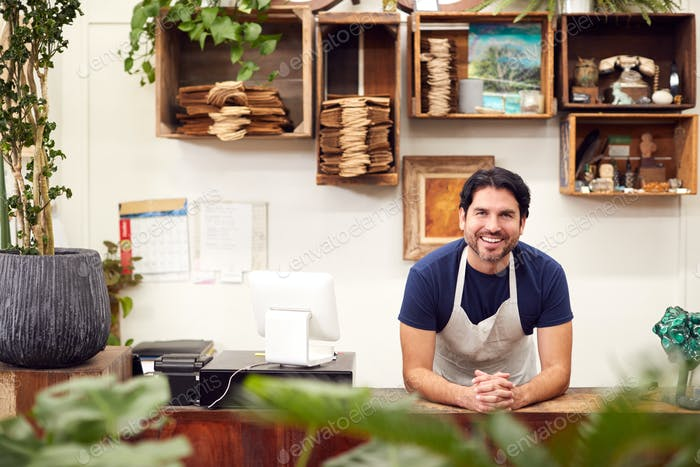 Portrait Of Smiling Male Sales Assistant Standing Behind Sales Desk Of Florists Store