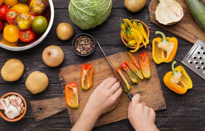 Hands using knife for chopping bell pepper