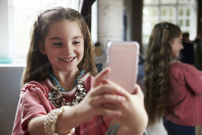 Girl Playing Dressing Up Game Taking Selfie On Mobile Phone