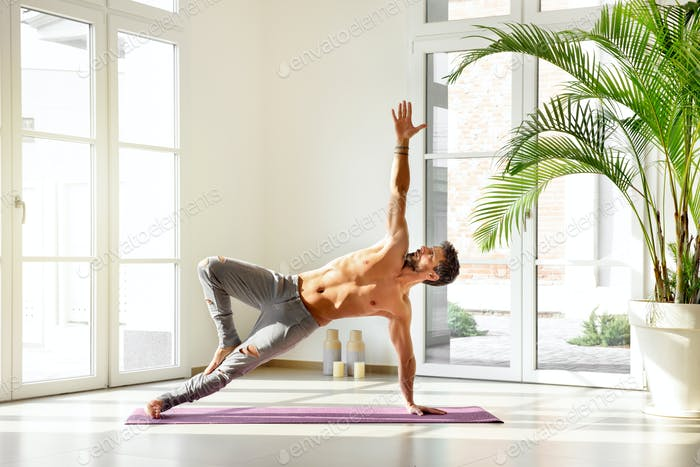 Man in side plank yoga pose with stretched arm