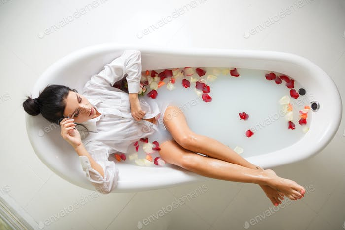 A young brunette woman takes a milk bath.