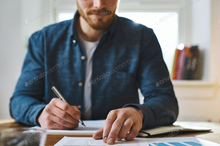 Unidentifiable man checking notes on desk
