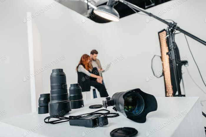 professional photographer and model with laptop in photo studio with digital photo camera, light