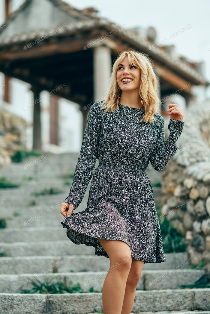 Smiling blonde girl wearing dress dancing outdoors.