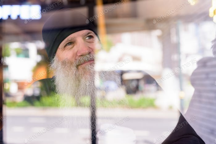 Face of mature handsome bearded hipster man thinking at the coffee shop through the window