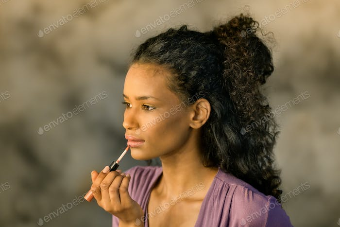 Attractive Dominican girl applying her makeup