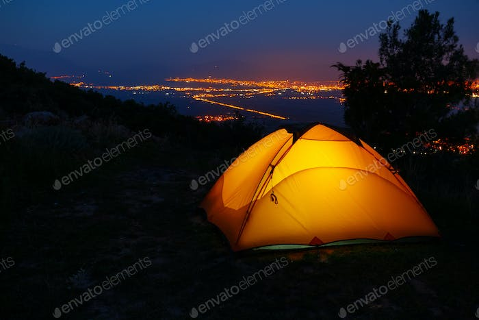 Orange lighted inside tent on mountain above city in night lights