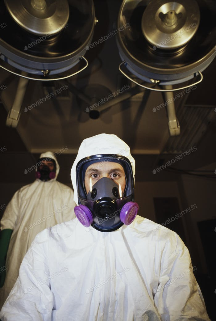 Two men wearing protective clean suits in a hospital room with lights on the ceiling.