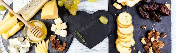 Banner of Assortment of cheese with walnuts, bread an honey on stone slate plate.