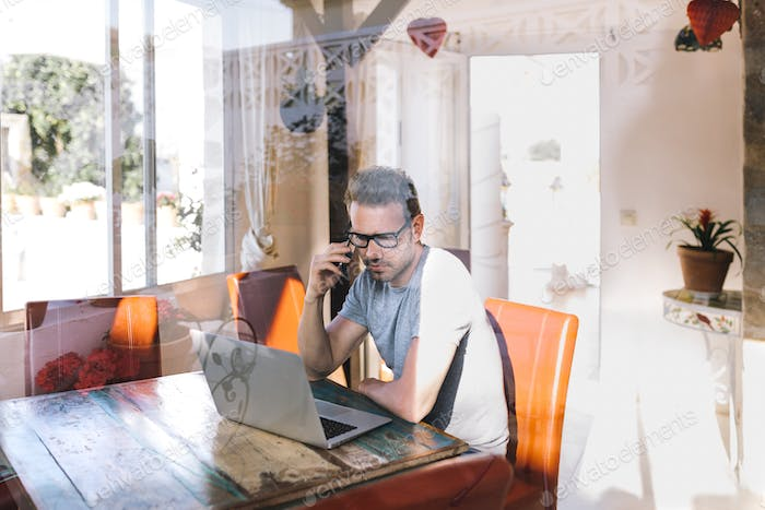 Businessman man working from home on the mobile phone