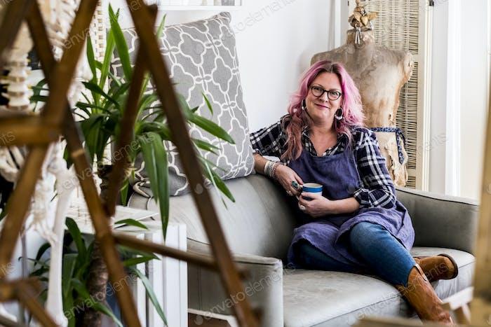 Lächelnde Frau mit langen blonden welligen Haaren mit rosa Streifen sitzt auf einem Sofa, Blick auf die Kamera.