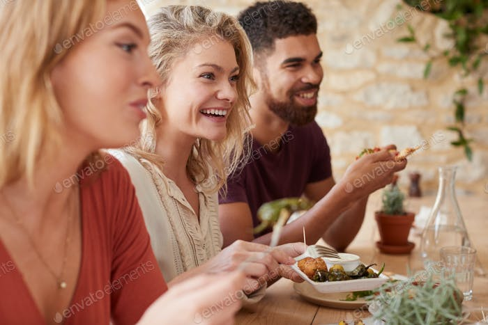 Three young adult friends eating in a restaurant, close up