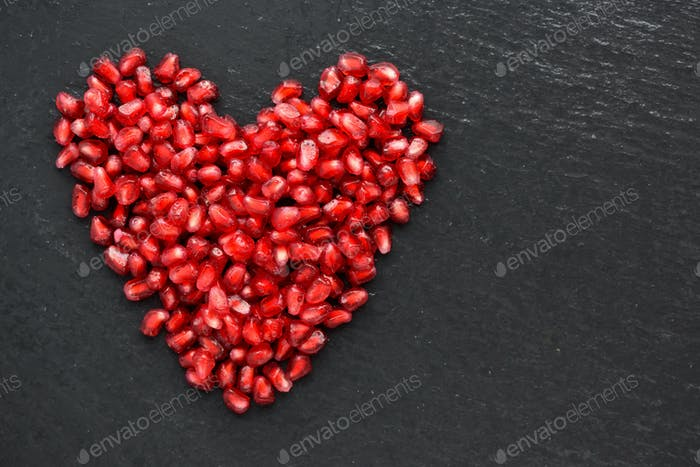 Pomegranate seeds over black stone background. Heart shape. Top
