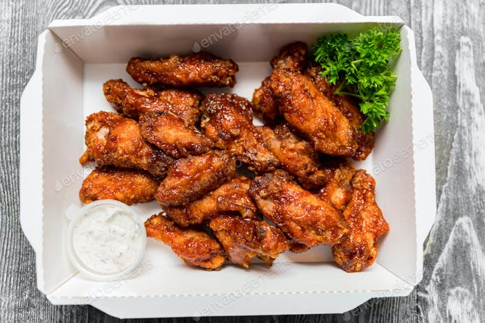 Fried chickens wings covered in honey, vegetables