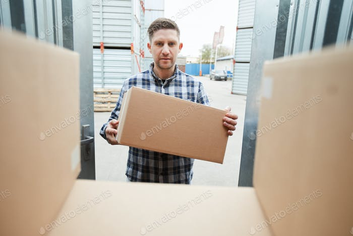 Man loading container with boxes