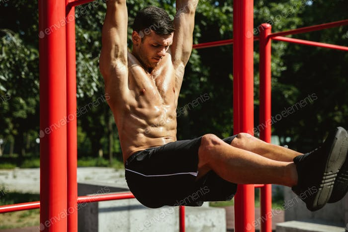 Young muscular man while doing his workout outside at playground