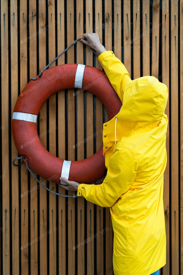 Man in yellow raincoat hangs a red lifebuoy on slatted wooden wall in the rain weather, back view