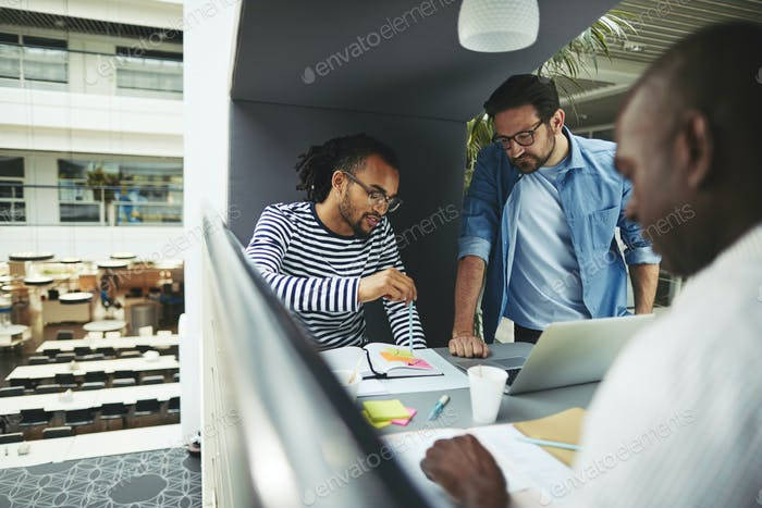 Businessmen discussing work while working in an office pod