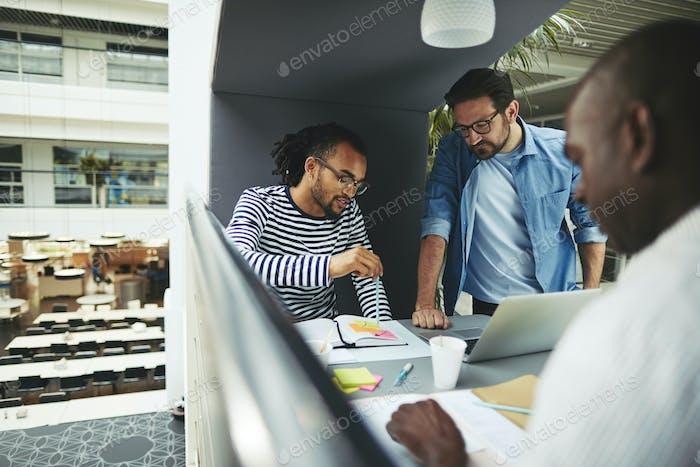 Geschäftsleute diskutieren Arbeit während der Arbeit in einem Büro-Pod