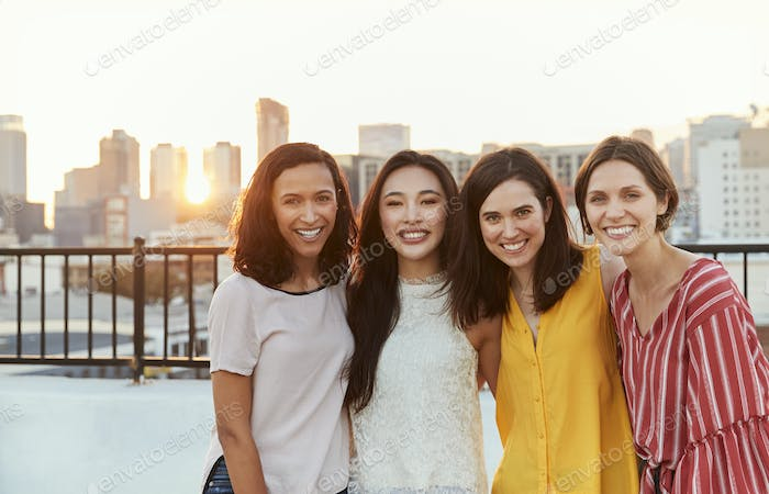 Portrait Of Female Friends Gathered On Rooftop Terrace For Party With City Skyline In Background