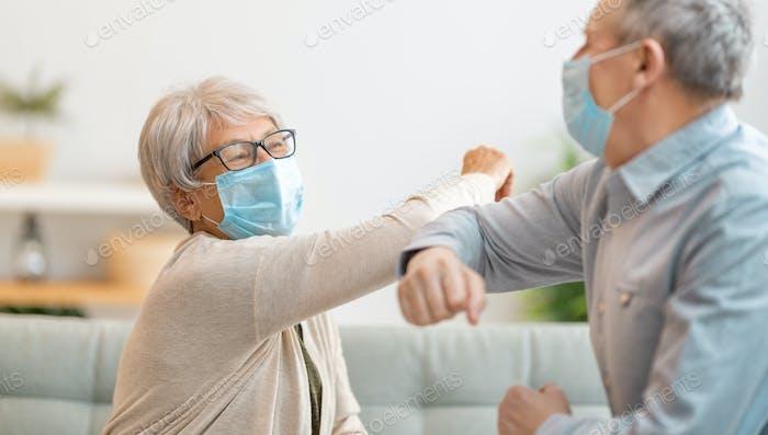 Senior couple greeting bumping elbows