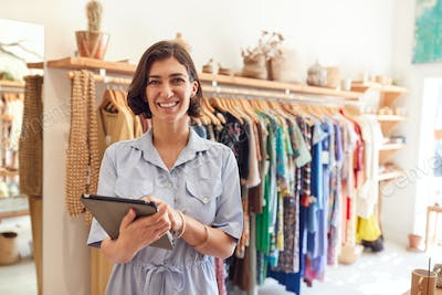 Portrait Of Female Owner Of Fashion Store Checking Stock In Clothing Store With Digital Tablet