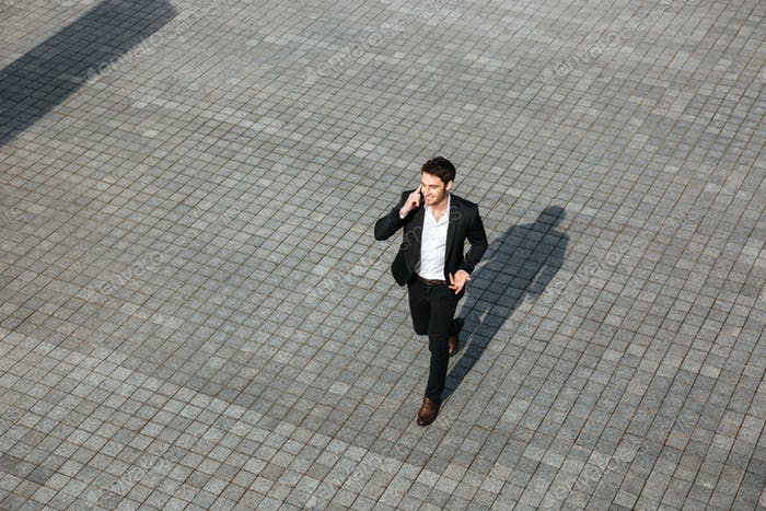 Happy young businessman walking outdoors