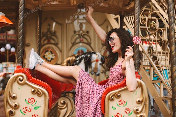 Fröhliche Dame in Sonnenbrille und Kleid halten Lolly Pop Süßigkeiten Reiten auf Karussell im Vergnügungspark