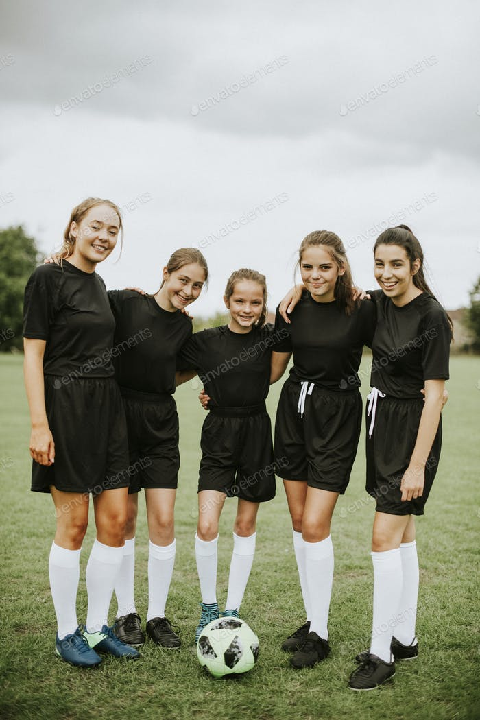 Female football players huddle before a match