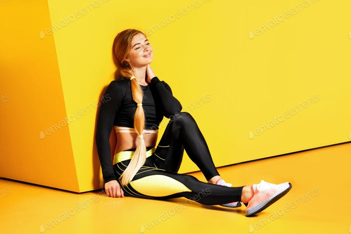 The athletic girl with long blond hair dressed in a stylish sportswear is sitting on the yellow