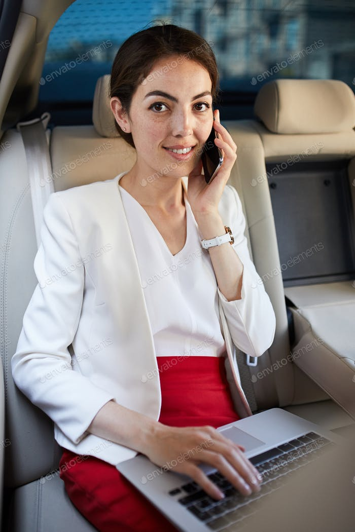 Young Businesswoman Speaking by Phone in Taxi