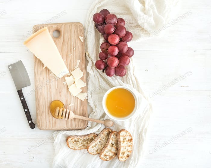 Parmesan cheese with grapes, honey and bread slices