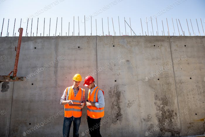 Civil engineer and architect dressed in orange work vests and helmets stand on a concrete wall